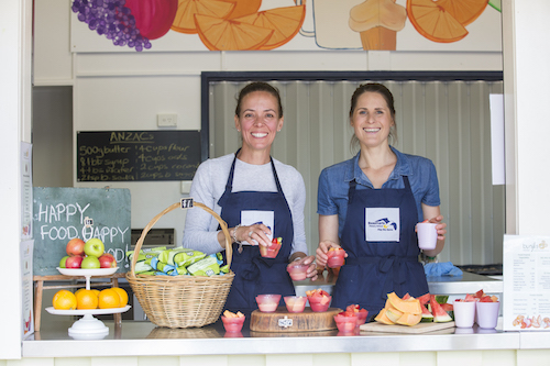 A photo of staff at the Beaumaris canteen holding up healthy food items.
