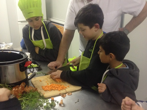 Three young boys in the kitchen, chopping vegetables with chef.