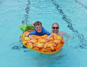 A photo of man and a boy in a swimming pool.