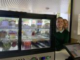 Two female students at the canteen counter, standing beside a fridge display case that contains healthy food.