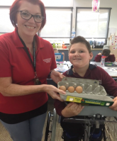 Teacher and a young boy with a walking device, holding a carton full of eggs.