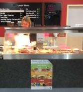 Bain marie in a food outlet, with a women standing behind it, preparing food. A poster on the front depicts the green, amber and red food categories.