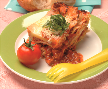 Vegetarian lasagne on a plate with fork and garnish