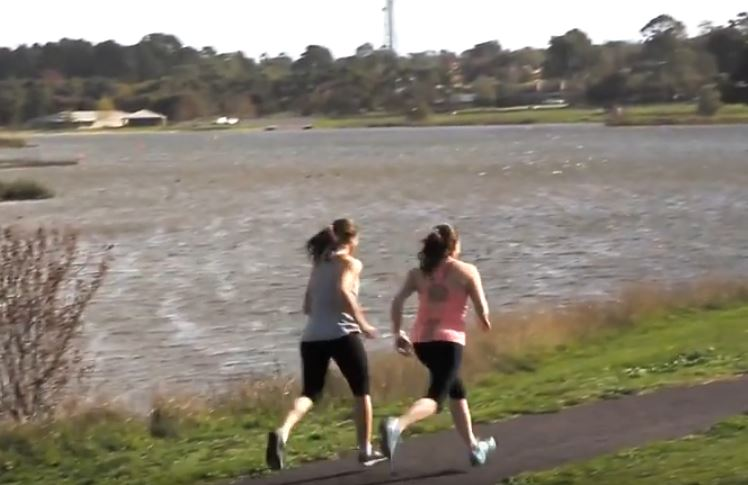 Two women running on a path beside a lake.