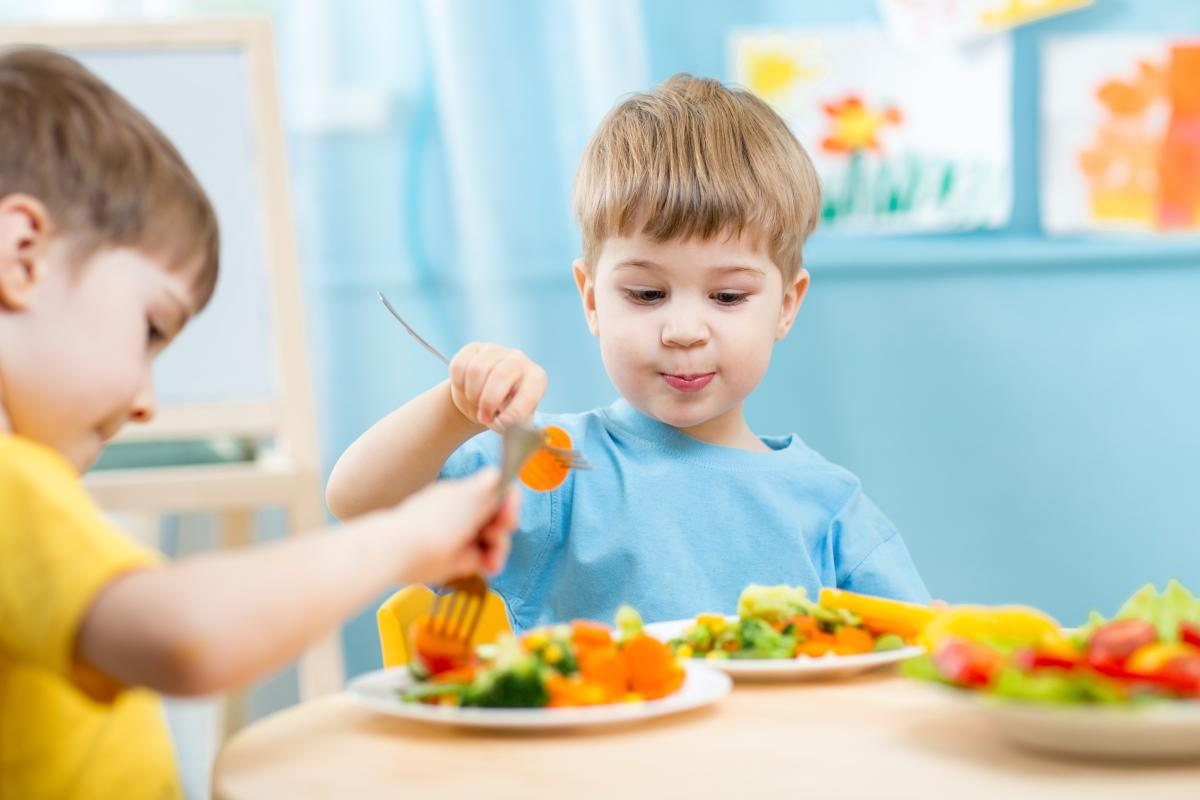A photo of two boys eating vegetables
