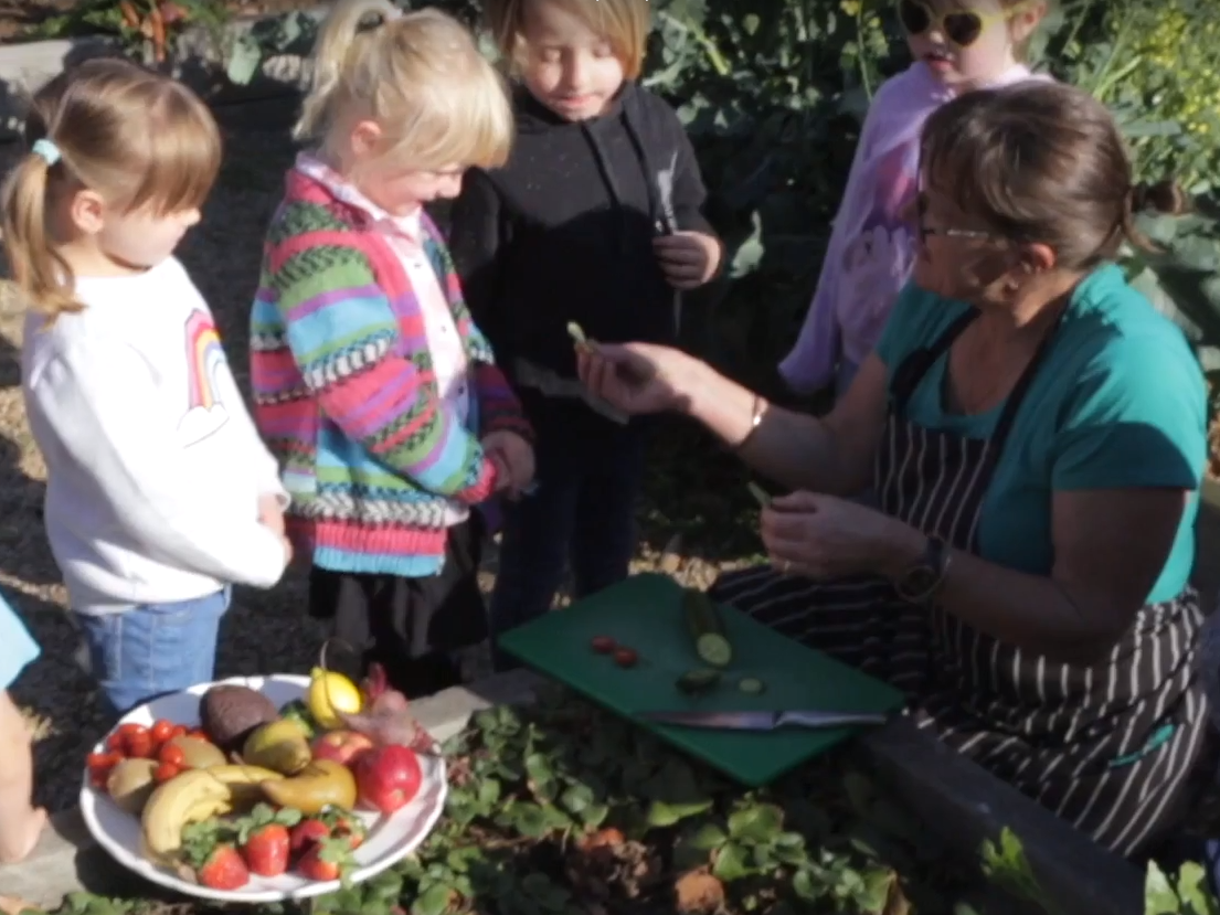 Child care educator showing children produce from the garden.