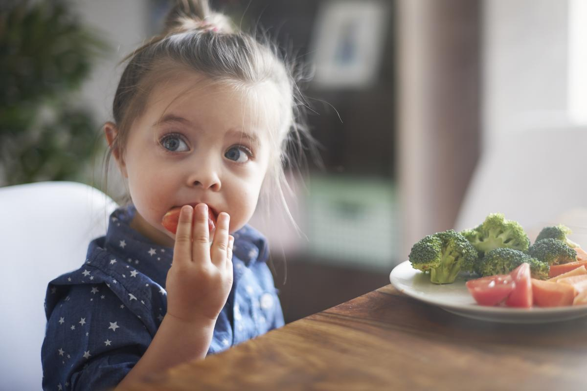 A photo of a young girl eating fruit
