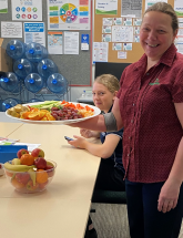 A photo of a woman holding a plate of fruit
