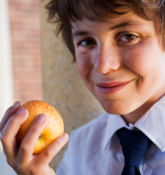 School boy holding apple
